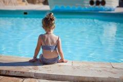 Det Yound barnet sitter på simbassäng Arkivfoto