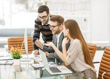 det yrkesmässiga affärslaget framkallar ett nytt projekt som sitter bak ett skrivbord i ett modernt kontor Arkivfoton