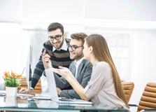 det yrkesmässiga affärslaget framkallar ett nytt projekt som sitter bak ett skrivbord i ett modernt kontor Royaltyfria Foton