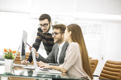 det yrkesmässiga affärslaget framkallar ett nytt projekt som sitter bak ett skrivbord i ett modernt kontor Arkivbilder