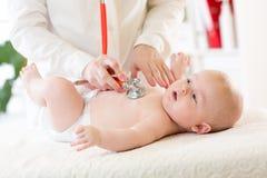 Det yrkesmässiga pediatriska undersökande spädbarnet behandla som ett barn Arkivbilder