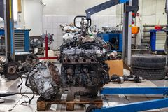 A detached engine suspended on a blue crane and a gear box on a lifting table in a vehicle repair shop. Auto industry. A detached engine suspended on a blue stock photography