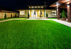 Detached house at night view from outside the rear courtyard. Detached luxury house at night - view from outside the rear courtyard with a green lawn royalty free stock photos
