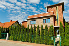 Detached house. Detached house with thujas fence Royalty Free Stock Images