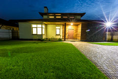 Detached luxury house at night view from outside front entrance. Royalty Free Stock Images
