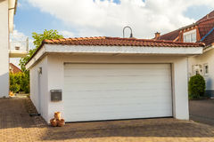 Detached white garage with orange brick tile roof Royalty Free Stock Image