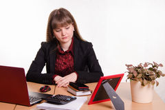 Detached woman sitting at office table Stock Photography