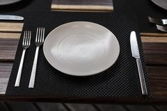 Detai of cutlery. Detail of plate and cutlery in a wood table after lunch royalty free stock photography
