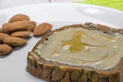 Detail über ein Brot mit Mandel-Butter und Honig stockfoto