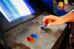 Detail über eine Hand, die Steuerknüppel nah an Kontrollen des blauen und roten Knopfes eines alten Weinlesesäulengangvideospiels Lizenzfreies Stockbild