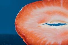 Detail über eine Scheiben-Erdbeere auf einem blauen Hintergrund lizenzfreies stockfoto