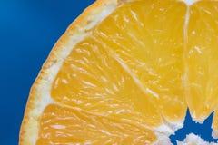 Detail über eine Scheiben-Orange auf einem blauen Hintergrund stockbilder