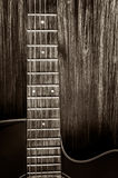 Detail of acoustic guitar in vintage style on wood background Stock Photo