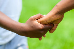 Detail of African boy holding girls hand. royalty free stock images