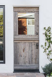 Detail of aged wooden door to a white home Stock Photos