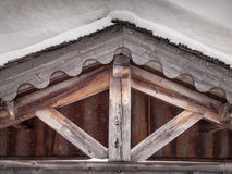 Detail of aged woodwork in the eaves of a snow covered roof Stock Images