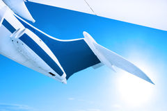Detail of aircraft tail fin. Airplane flying against a blue sky, close up of tail fin and engines Stock Photo