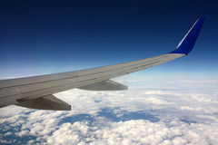 Detail of aircraft wing. Above clouds Stock Photo
