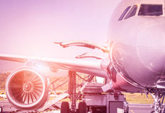 Detail of airplane at terminal gate before takeoff. Travel concept and wander around the world in international airport at sunset - Vintage marsala filtered royalty free stock photography