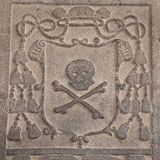 Detail of an ancient carved stone frame with with skull and bone. Detail of an ancient ornamental carved stone frame with skull and bones in portuguese style stock photos