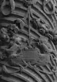Detail on an ancient column with some winged creatures. Shot in black and white detail of the sculpture on the facade of this historic building cathedral Stock Photos