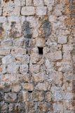 Detail of Ancient Stone Block Walls, Dubrovnik, Croatia. Detail of ancient massive rough stone block walls, with defensive arrow slit or embrasure, medieval stock photos