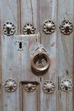 Detail of knocker and lock of ancient wooden door. Detail of ancient wooden door of church San Mateo, from Fifteenth century, with ring knocker and lock, in Royalty Free Stock Photo