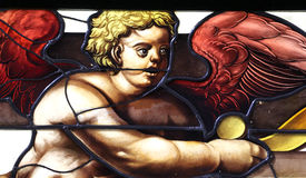 Detail of an angel from a stained glass window. A detailed view of an angel with red wings, from a stained glass window, landscape cut stock image