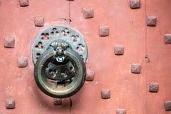 Detail of antique bronze door knocker on old red door Stock Photo
