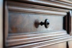 Detail of an antique wood furniture. With focus on the metallic knob of the drawer Royalty Free Stock Photography