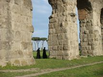 Detail of arches of a Roman aqueduct with in distance two walking priests. Rome. Italy. Royalty Free Stock Photo