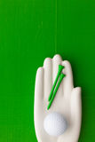 Detail of artifical hand with golf equipments Royalty Free Stock Photo