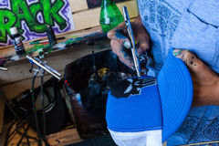 Detail of an Artist with airbrush coloring a blue hat. Artist with airbrush coloring a blue hat. this artist is painting a blue hat with an airbrush to add a Royalty Free Stock Image