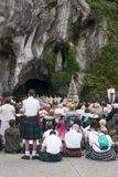 Detail of the assistants to the holy mass. LOURDES, FRANCE - JULY 6, 2016: Details of those attending the Holy Mass, volunteers and pilgrims, near the Shrine of stock photography