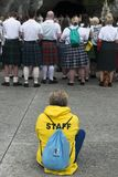 Detail of the assistants to the holy mass. LOURDES, FRANCE - JULY 6, 2016: Detail of the assistants to the holy mass Some with a Scottish skirt, near the stock photo