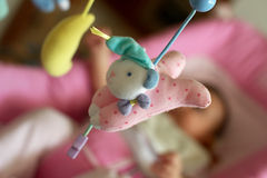 Detail of a baby mobile. Close up of a peluche bear part of a baby mobile, baby blurred on the background Royalty Free Stock Image
