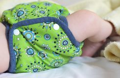 Detail of baby´s hip dressed in green cloth diaper Royalty Free Stock Photos