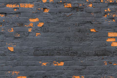 Detail, background – old black wall with red bricks showing th. Wall painted black, with the black paint peeled away to show some bricks Royalty Free Stock Photography