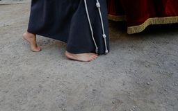 Detail on a barefeet penitent during an easter holy week procession in mallorca detail on hoods vertical. A barefoot penitent takes part in the procession of royalty free stock images