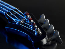 Detail of a bass guitar. With blue light in black back royalty free stock images
