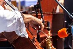 Detail of bass musical instrument. Artistic performances at folk festivals. Cellist musician group perform music in the street, cl. Ose up man playing violin stock images