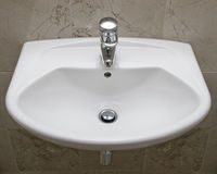 Detail of a bathroom appliance. Detail shot of white ceramic hand wash basin in a marble bathroom Stock Images