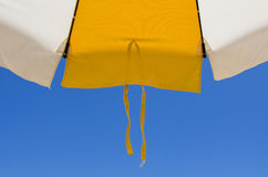 Detail of a beach umbrella with lace on the bottom of the blue s Stock Photos