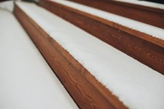 Detail of beams in cabin wall. Painted wood with fungicide paint. The railing of the veranda another view close with the snow another view royalty free stock images