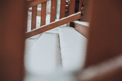 Detail of beams in cabin wall. Painted wood with fungicide paint. The railing of the veranda close with the snow another view stock photography