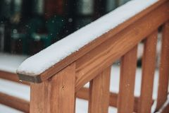 Detail of beams in cabin wall. Painted wood with fungicide paint. The railing of the veranda closeup with the snow another view royalty free stock image