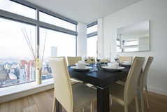 Detail of a beautiful dining area. With wooden dining table and white leather chairs Stock Photos