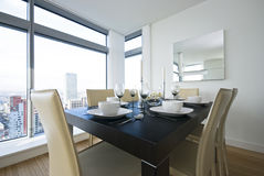 Detail of a beautiful dining area set up. With wooden dining table and white leather chairs Stock Images