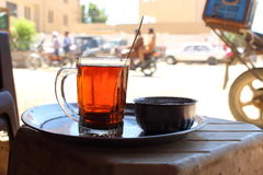 Detail of a bedouin cup of tea with bikes and people in the streets on soft background, Bahariya Oasis, Egypt Stock Photos