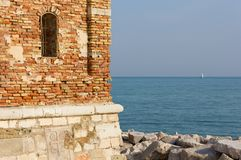 Detail of a Bell Tower in Caorle against the Adriatic Sea. Detail of the bell tower of the Shrine of Our Lady of the Angel in Caorle, Italy, with the Adriatic royalty free stock photo